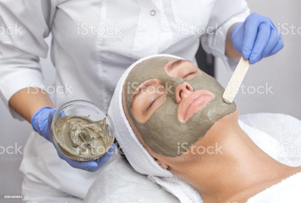La procédure pour appliquer un masque d'argile sur le visage d'une belle femme. - Photo