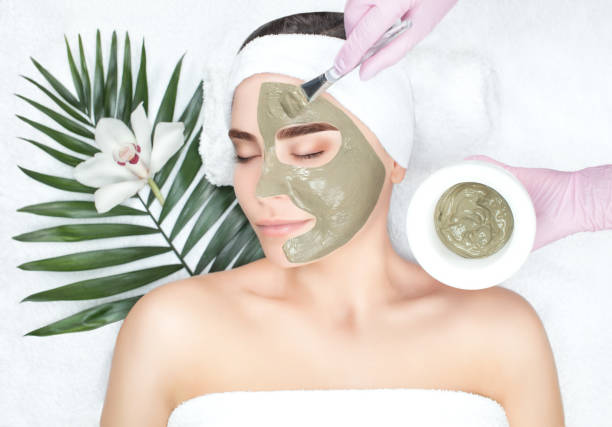 The procedure for applying a mask from clay to the face of a beautiful woman stock photo