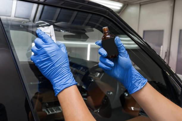 用海綿和男性工人在車窗上塗上納米陶瓷塗層,對車窗施加疏水性效果的過程。圖像檔