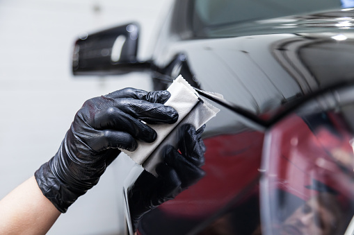 The process of applying a nano-ceramic coating on the car's fender by a male worker with a sponge and special chemical composition to protect the paint on the body from scratches, chips and damage.