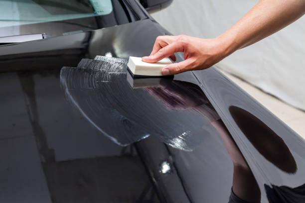 一名男性工人用海綿和特殊化學成分在汽車引擎蓋上塗上納米陶瓷塗層,以保護車身上的油漆免受劃痕、碎屑和損壞。圖像檔