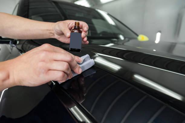 男工人用海綿和裝有特殊化學成分的瓶子在汽車引擎蓋上塗上納米陶瓷塗層,以保護車身上的油漆免受劃痕和碎屑的影響。圖像檔