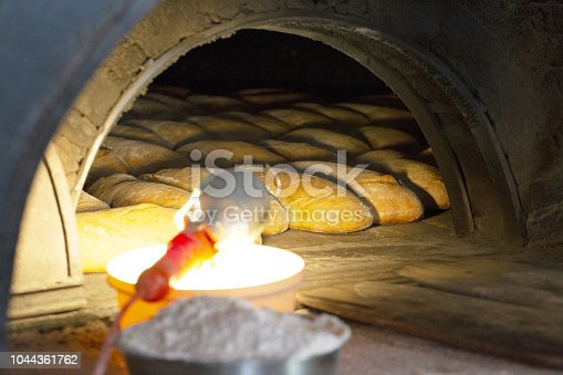886308526 istock photo The process of baking bread in an old traditional oven. 1044361762