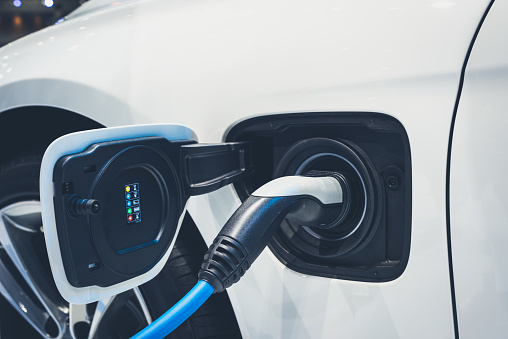 The Process Of Charging An Electric Vehicle Electric Car Socket For Background Stock Photo - Download Image Now
