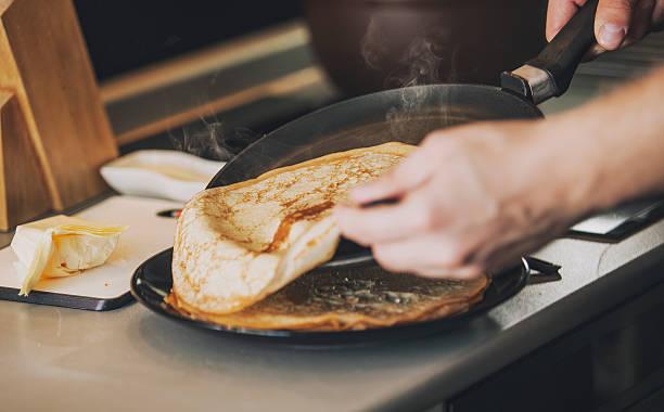 the process of cooking pancakes on a skillet - frying pan bildbanksfoton och bilder