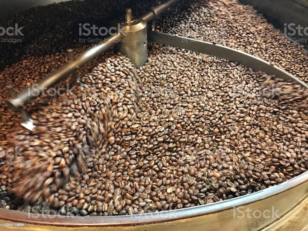 The process of cooling coffee beans after roasting. Coffee beans are mixed in special equipment. Background. Texture. stock photo