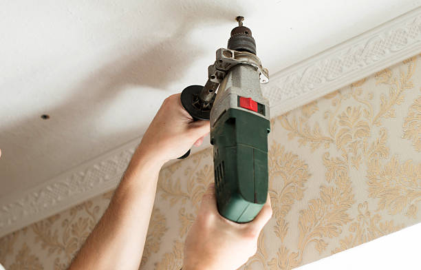 The process of drilling with an electric drill The process of drilling a white plaster ceiling with an electric drill plaster ceiling design stock pictures, royalty-free photos & images
