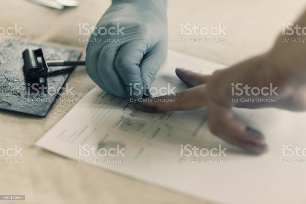 The process of getting samples of fingerprints hands for further study stock photo