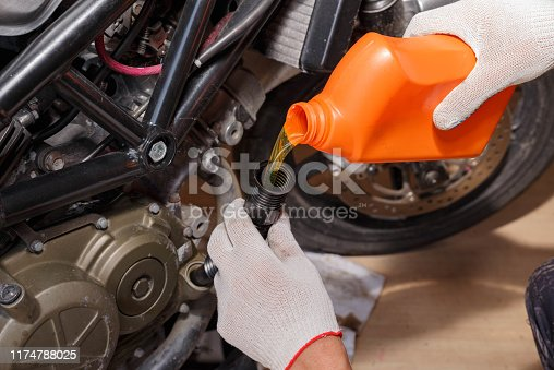 The process of pouring new oil into the motorcycle engine. Motorcycle service.