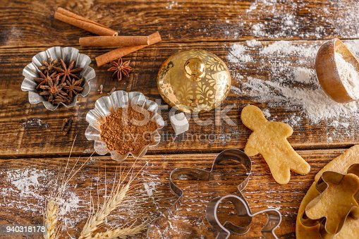 The process of preparation of classic ginger biscuits in the form of little men. Still life on a wooden background. View from above.