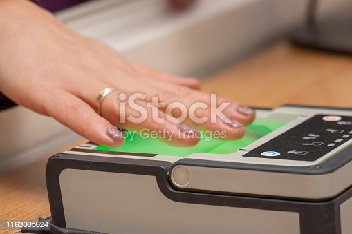 The process of scanning fingerprints during the check at border crossing. Female hand puts fingers to the fingerprint scanner. Identity verification and border control, immigration concept