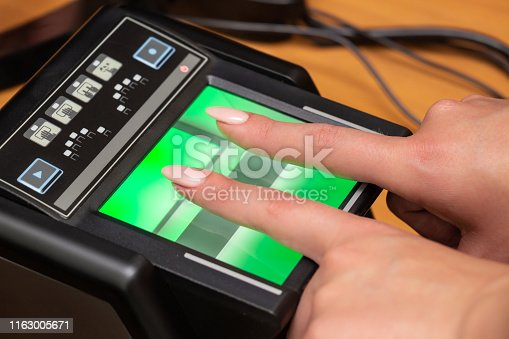 The process of scanning fingerprints during the check at border crossing. Female hand puts fingers to the fingerprint scanner. Biometric, identity verification and border control, immigration concept