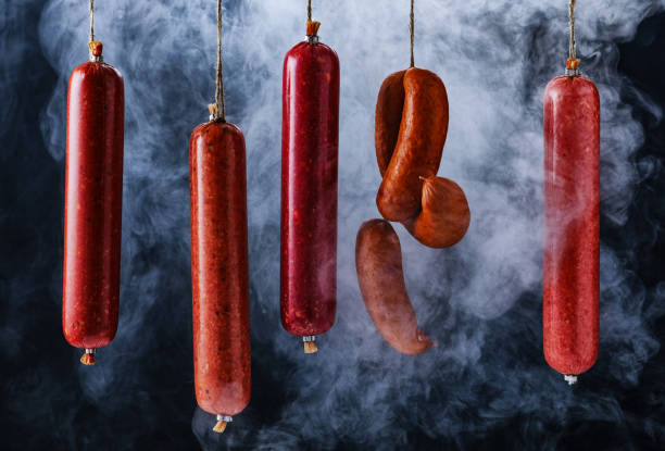 Cтоковое фото The process of smoking sausage. Smoked sausages hang in a cupboard with smoke
