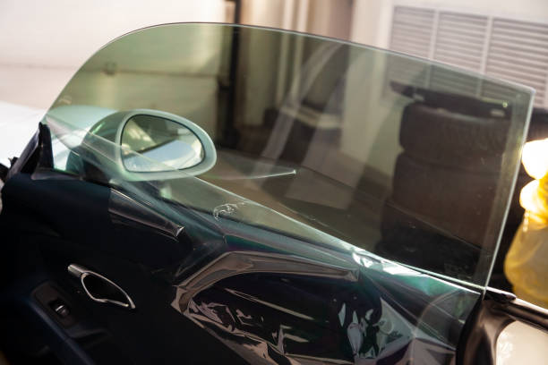 在車間內對汽車玻璃進行著色的過程, 以便用未卡住的保護膜安裝額外的設備圖像檔