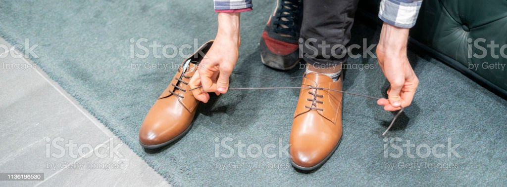 the process of tying shoelaces on brand new boots