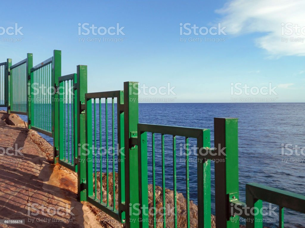 The protective fence next to walking trail along the cliffs stock photo
