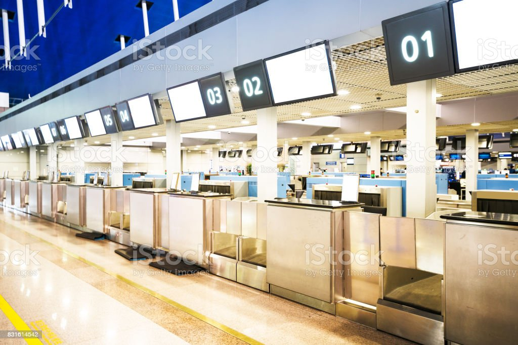 The public check-in area with crowd control barriers of the city airport at early morning time. stock photo