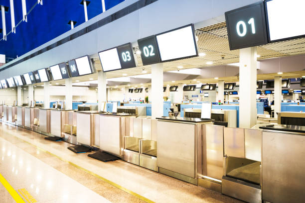 the public check-in area with crowd control barriers of the city airport at early morning time. - airport check in counter stock pictures, royalty-free photos & images