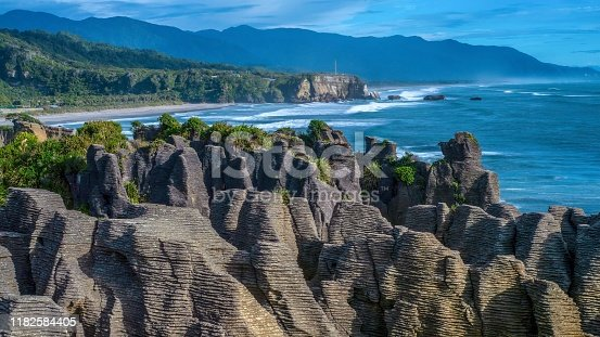 In the foreground is a large set of unusual pinnacle rock formations on land, with grooves eroded into the limestone by water coming through a blowhole, making them look like pancakes. In the background is a beautiful seascape, with a beach, cliff, and low mountain range, while waves from the Tasman Sea break along the shoreline.
