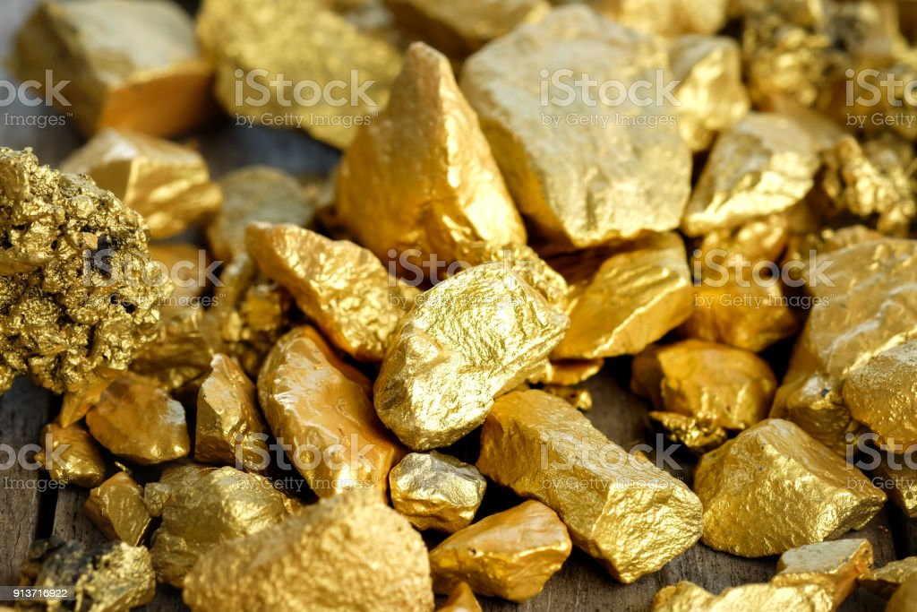 The pure gold ore found in the mine on a wooden floor stock photo