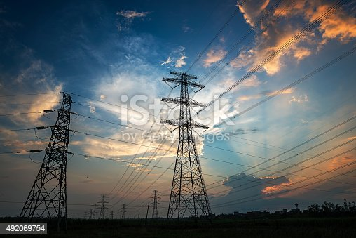 Electricity Pylon power line transmission tower at sunset