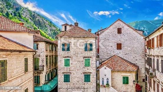 A pretty summer scene of old, traditional European buildings in a historical neighborhood, with painted wooden shuttered windows, stone walls, and terracotta tiled roofs. The town is set in a valley between steep, green hills and the sky is a vibrant blue.