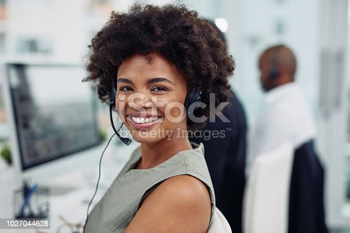 Portrait of a call centre agent working in an office with her colleagues in the background