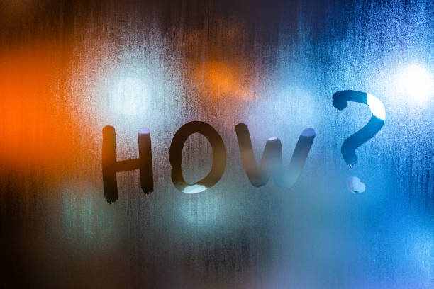 the question how written by finger on wet glass with blurred lights in background stock photo