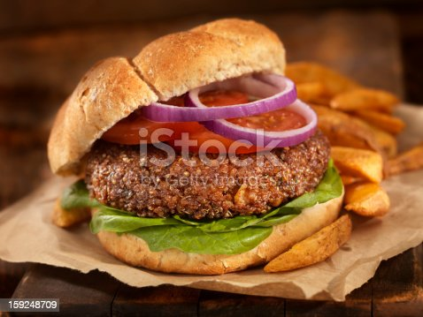 A fantastic vegetarian burger made with quinoa, chick peas, rolled oats, crushed onions and garlic, spices on a Whole Wheat Bun with spinach, tomatoes and onion and a side of Oven Baked French Fries -Photographed on Hasselblad H3D2-39mb Camera