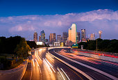 Long exposure of evening rush hour with cars racing in and out of Downtown Dallas, Texas on a stormy night.