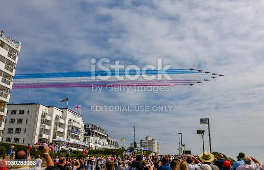 Bournemouth, UK. 1 September 2018. The RAF Red Arrows fly over a hotel and crowds of spectators at the Bournemouth Air Festival on a sunny day. A free annual air festival.