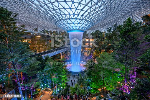 People watching the Rain Vortex, a 40m-tall indoor waterfall located inside the Jewel Changi Airport in Singapore.