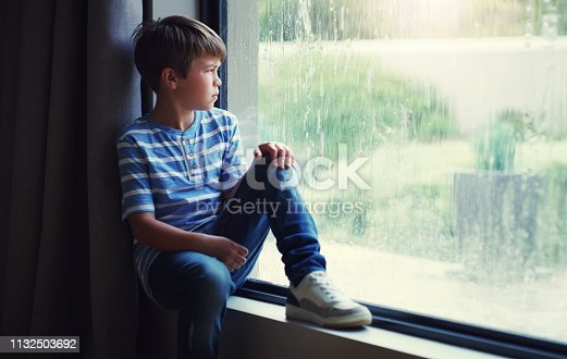 Shot of a sad young boy watching the rain through a window at home
