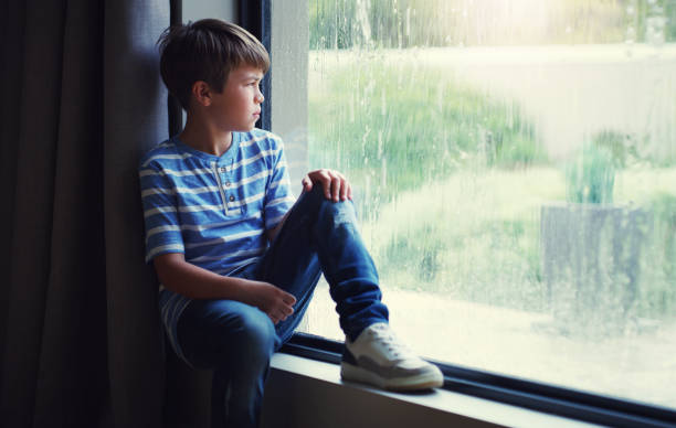 the rain washed away his fun for the day - boy looking out window stock pictures, royalty-free photos & images
