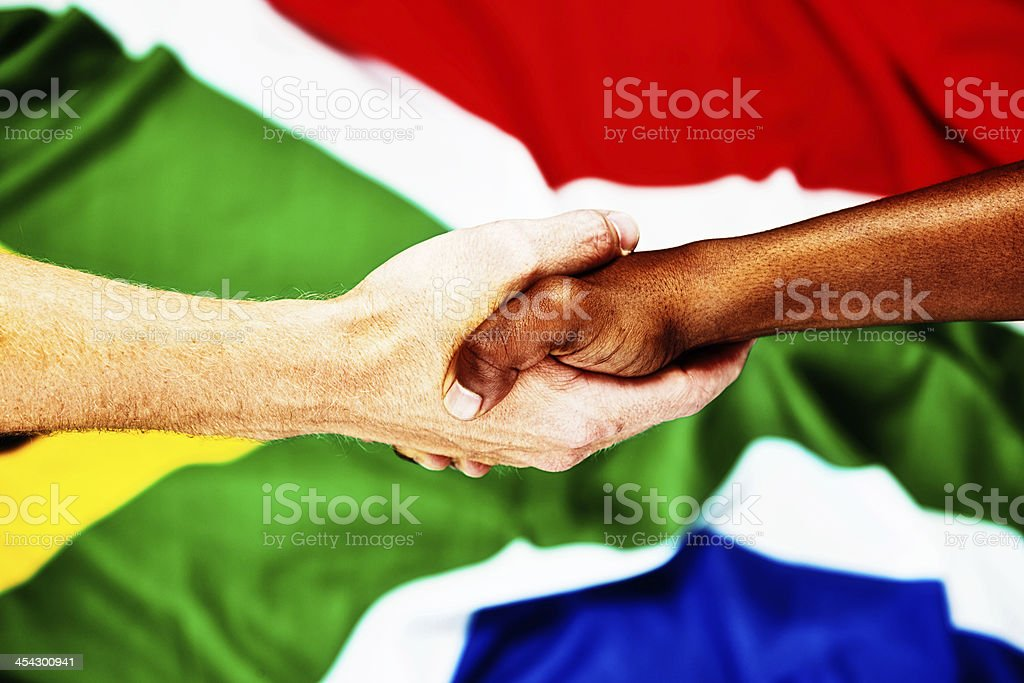 The Rainbow Nation: interracial handshake against South African flag royalty-free stock photo