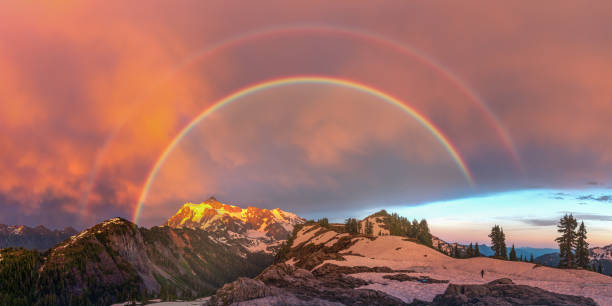 The rainbow over stormy mountains at dusk stock photo
