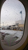 The raindrops on the airplane window. View from the inside of cabin with a grey sky background. The outside can see the wing of the aircraft and building.