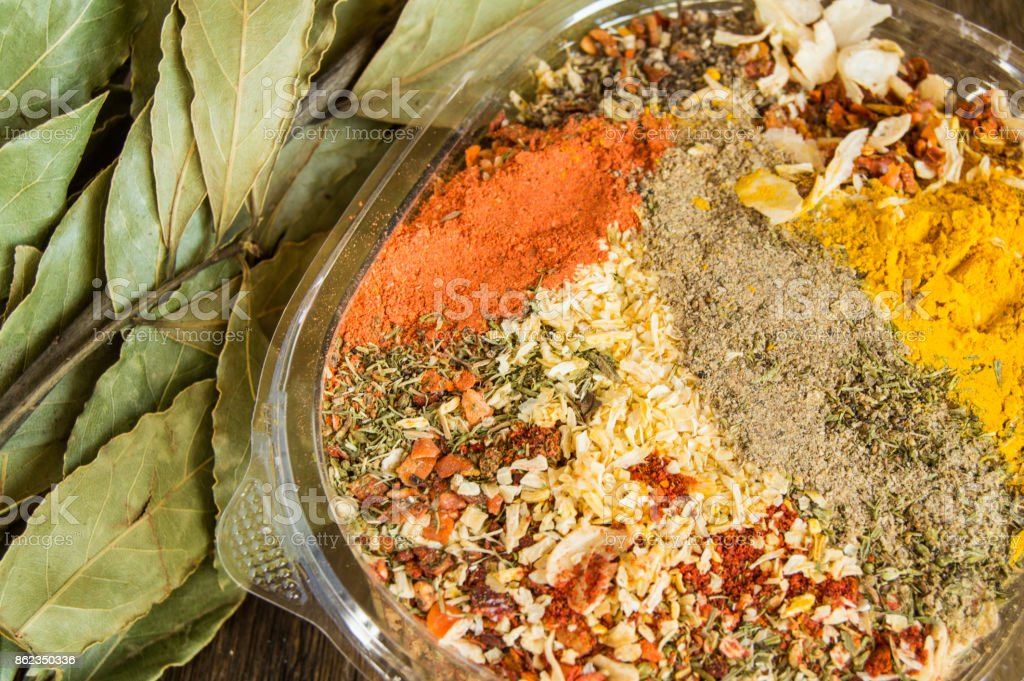 The range of Oriental spices with spicy chilli, curry and a mixture of other spices. Copy space, old dark wooden background and branch of Bay leaf stock photo