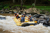 Group of nine men white water river rafting together in a forested valley in Japan.