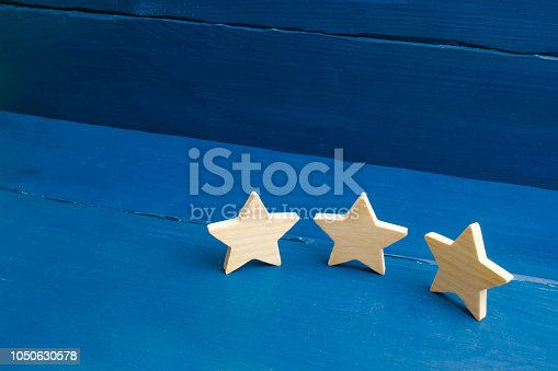 istock The rating of the hotel, restaurant, mobile application. Three stars on a blue background. The concept of rating and evaluation. Quality service, buyer choice. Success in business 1050630578