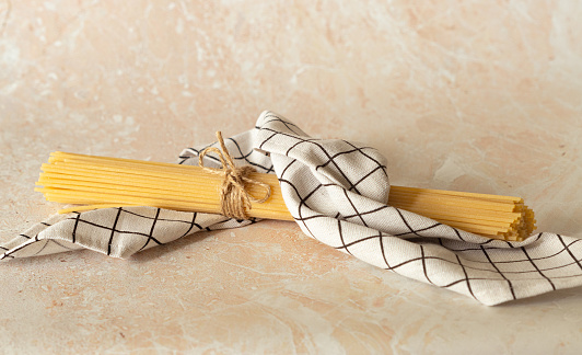 the raw spaghetti is wrapped in a checkered towel and tied with a rope. Italian wheat pasta on a light marble background