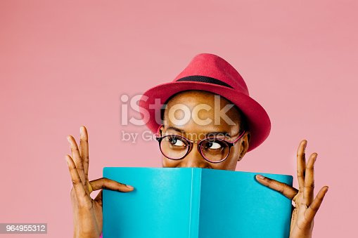 Portrait of a young woman holding a blue note book and looking up, full of joy and happiness, isolated on pink studio background