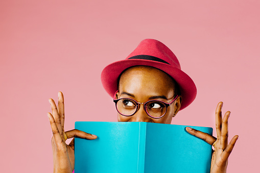 istock The reader: Portrait of a happy young woman full of joy holding a book 964955312