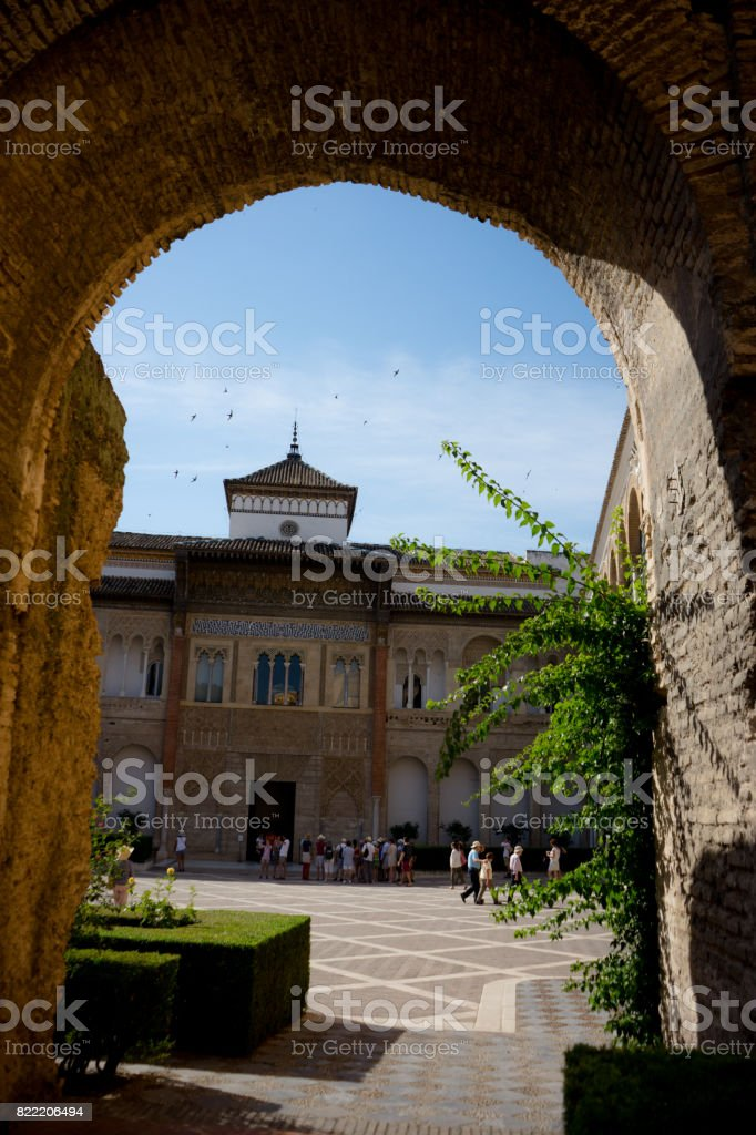 Seville, Spain - June 19: The real Alcazar, Seville, Spain on June 19, 2017. Tourists walking in the courtyard on a warm summer day. stock photo