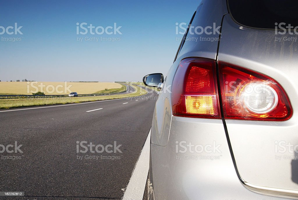 The rear end of a car traveling down a road stock photo