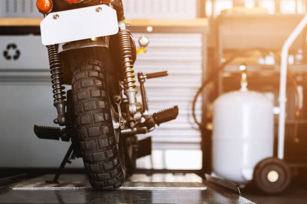 the rear of the classic motorcycles standing in repair shop with soft-focus and over light in the background – zdjęcie