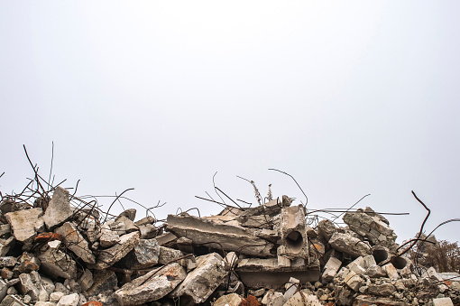 The rebar sticking up from piles of brick rubble, stone and concrete rubble against the sky in a haze. Remains of the destroyed building. Copy space.
