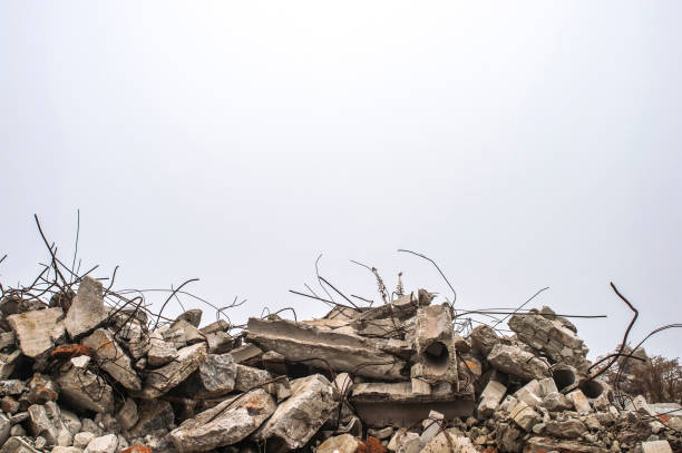 the rebar sticking up from piles of brick rubble, stone and concrete rubble against the sky in a haze. - destruição imagens e fotografias de stock