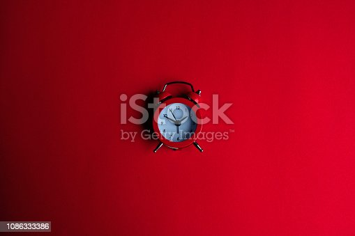 istock The red alarm clock on the red background. 1086333386