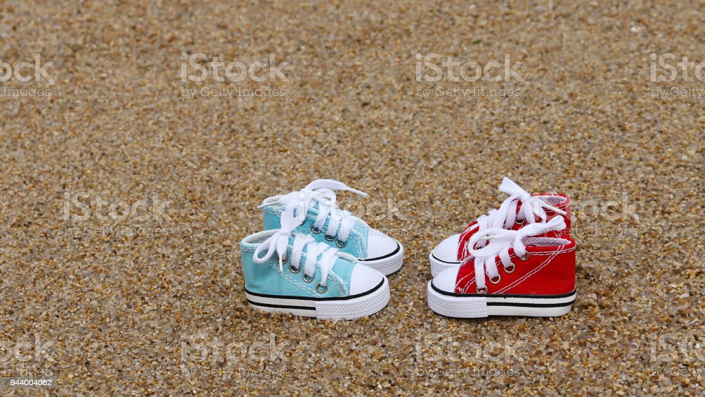 The red and blue sneakers on the sand. stock photo